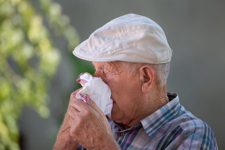 Senior man blowing nose in textile tissue in courtyard. Allergy and sickness concept Stock Photo