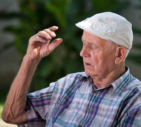 senility: Portrait of senior man talking and explaining something with hand in courtyard Stock Photo
