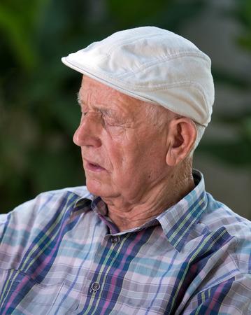 Senior man fall asleep in courtyard in summer time