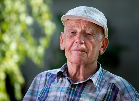 Portrait of old man in his 80s in shirt and modern cap sitting in park