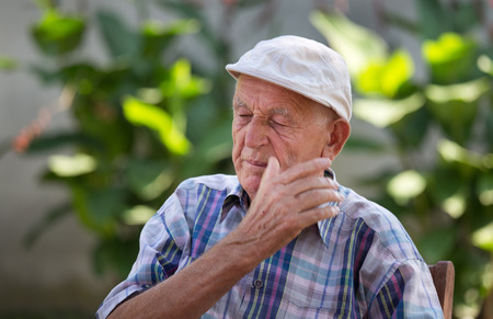 disgusted: Old depressed man with disgusted face expression in courtyard Stock Photo