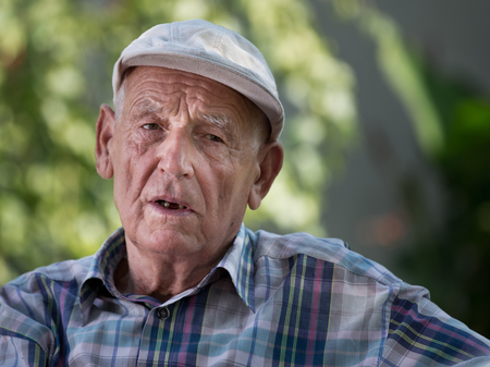 conceived: Portrait of old depressed man in garden. Concept of mental problems