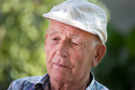 Portrait of old depressed man in garden. Concept of mental problems
