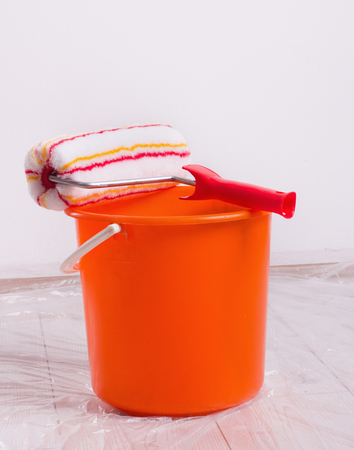 roller brush: Roller brush for wall painting and bucket on protected wooden floor with foil in the room