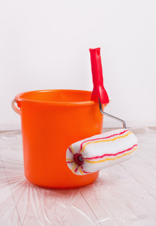 Roller brush for wall painting and bucket on protected wooden floor with  foil in the room