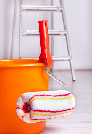brush painting: Roller brush and bucket for painting wall and ladder in background in the room Stock Photo