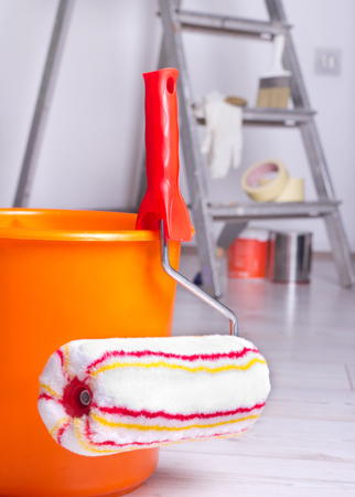 roller brush: Roller brush and bucket for painting wall and ladder in background in the room Stock Photo