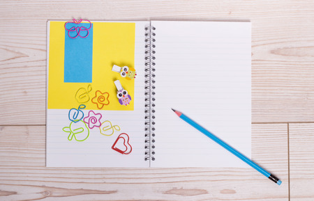 paperclips: Open notebook with pencil note paper and cute colorful paperclips on wooden desk