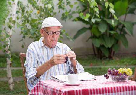 gerontology: Senior man sitting in courtyard with newspaper on table and eating ripe white grape Stock Photo