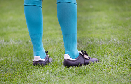 uniform green shoe: Close up of soccer players legs with blue socks and football boots standing on grass
