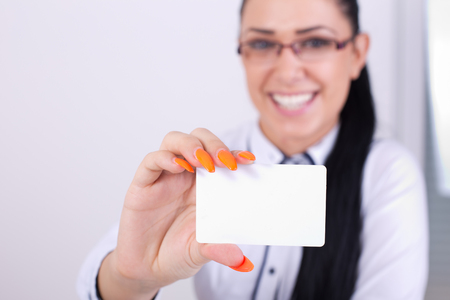 businesscard: Close up of female hand holding blank businesscard. Young pretty business woman blurred in background