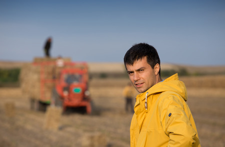 Portrait of attractive farmer standing in front of tractor with soybean bale used as alternative energy for heating