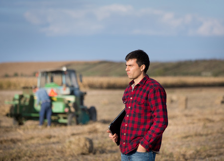 conceived: Conceived young farmer with laptop standing in harvested soybean field during baling process