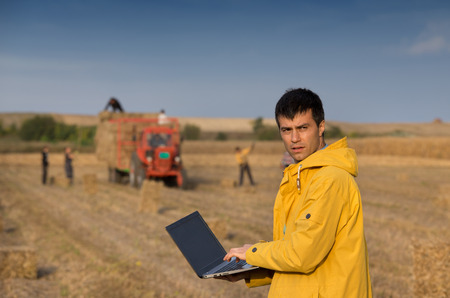 conceived: Conceived young farmer with laptop standing in harvested soybean field while workers loading tractor trailer with bales Stock Photo
