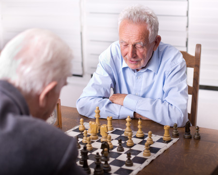 conceived: Two senior men playing chess in the room Stock Photo