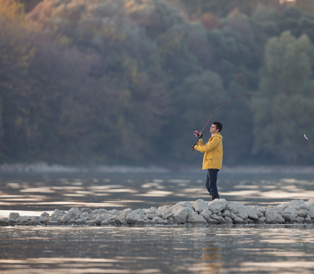 waders: Young man fishing on the river in autumn time