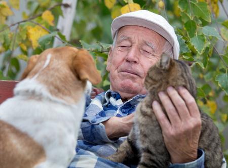 Senior man enjoying tender moments with his cat and dog, cuddling them in courtyard Zdjęcie Seryjne