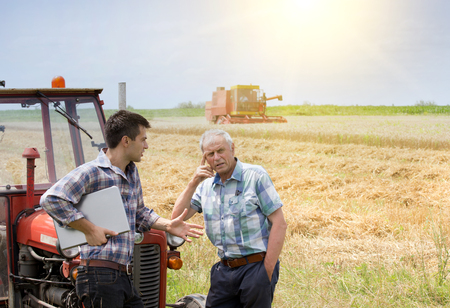 Two farmers leaning on tractor and thinking about solving problem in the field. Combine harvester working in background Standard-Bild
