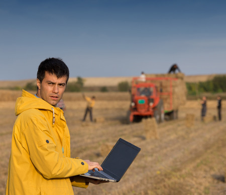 Attractive farmer with laptop standing in front of tractor with soybean bale used as alternative energy for heating