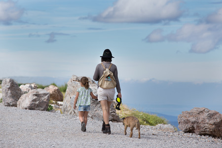 Mother and daughter walking with dog on mountain peak and looking at countryside