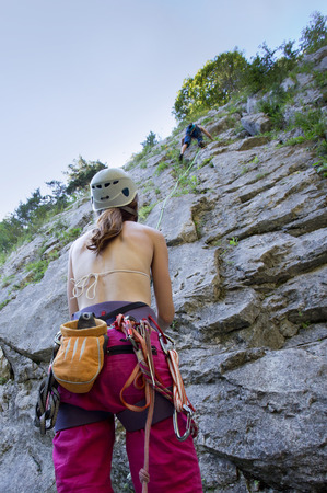 ensuring: Girl with rope and other climbing gear ensuring friend climbing on the rock