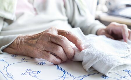 senescence: Close up of old womans wrinkled hand on table Stock Photo