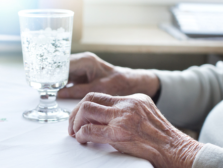 senescence: Close up of old womans wrinkled hands on table with glass of water Stock Photo