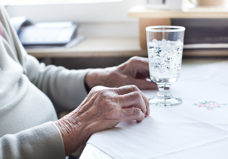 women s health: Close up of old womans wrinkled hands on table with glass of water Stock Photo