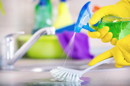 Close up of human hand in protective gloves holding scrubbing brush and spray bottle and washing kitchen countertop. Faucet and cleaning supplies in background Stock Photo
