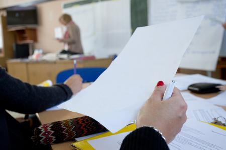 curso de capacitacion: Cerca de la mano femenina que sostiene el papel en el curso de formación con profesor en el fondo