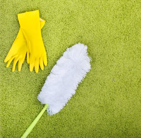 Top view of green fluffy carpet with duster and rubber gloves. Spring cleaning concept