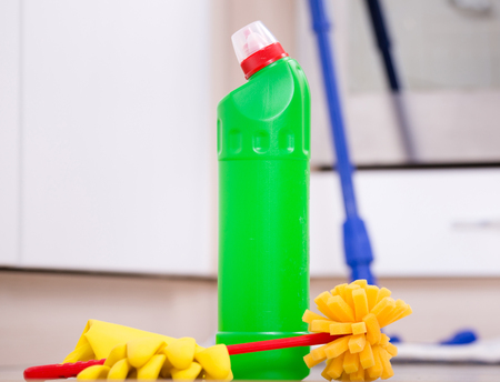desinfectante: Close up of bottle with disinfectant, protective gloves and brush on kitchen floor and oven in background. House cleaning concep Foto de archivo