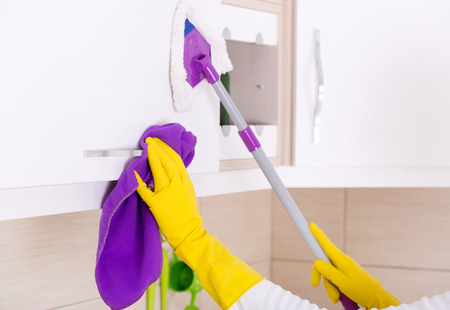 cabinets: Close up of human hands cleaning and dusting kitchen cabinets Stock Photo