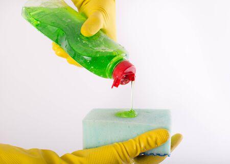 lavar platos: Cerca de las manos humanas con guantes de protección verter detergente para lavavajillas en una esponja. Aislado en el fondo blanco
