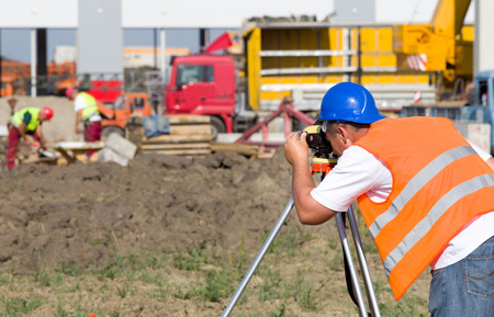 tacheometer: Surveyor engineer working with theodolite on road construction site Stock Photo