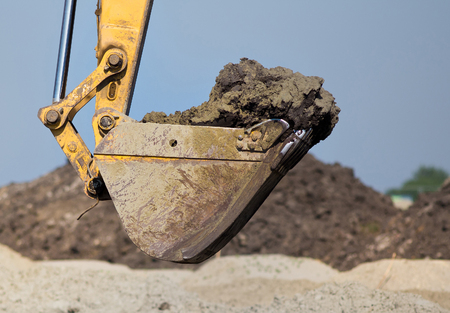 Close up of excavator bucket loaded with dirt. Dredger working at construction site