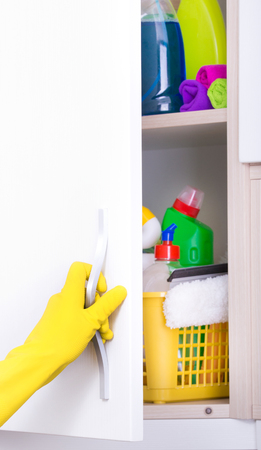 Close up of hand with rubber gloves opening door of cleaning supplies pantry