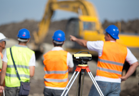 geodetic: Theodolite on tripod at road construction site with engineers supervising works