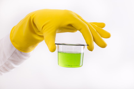 Hand with rubber glove holding dosage cup with green detergent against white background. Safety cleaning products usage indoor