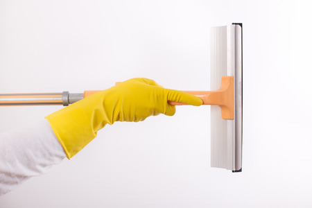 Woman with rubber gloves holding squeegee for windows cleaning, isolated on white background Stock Photo