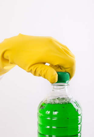 unscrewing: Hand with rubber glove unscrewing bottle with cleaning product against white background Stock Photo