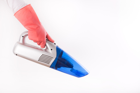 handheld device: Close up of female hand with rubber gloves holding cordless vacuum cleaner isolated on white background