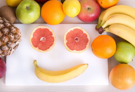 Smiley face made from grapefruit slices and banana on white boar rounded with different fresh fruits. Healthy eating concept
