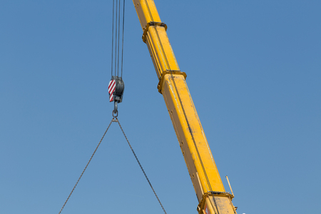 lifting hook: Detail of hook of the crane lifting load against blue sky at construction site Stock Photo