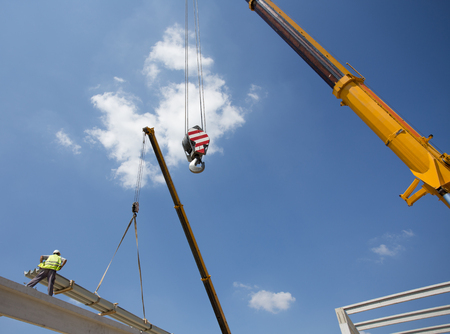 Construction worker standing on concrete truss and placing roofing material lifted by crane Stock Photo