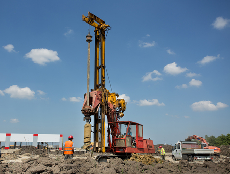 Hydraulic drilling machine boring ground at construction site Stock Photo