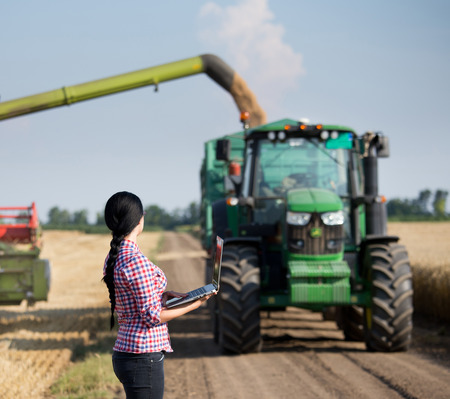agronomist: Pretty young farmer woman with laptop standing in front of tractor with trailer and combine harvester at summer field work Stock Photo