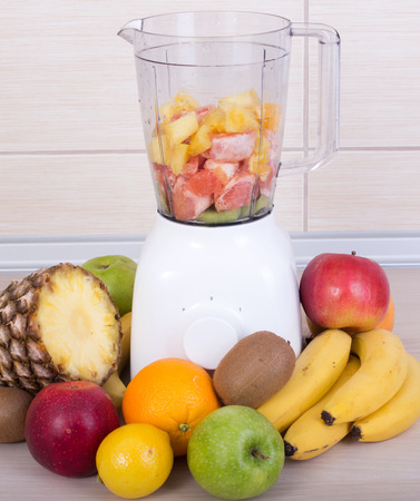 cocktail mixer: Preparing smoothie in white blender with different fresh fruits on kitchen countertop. Healthy eating concept