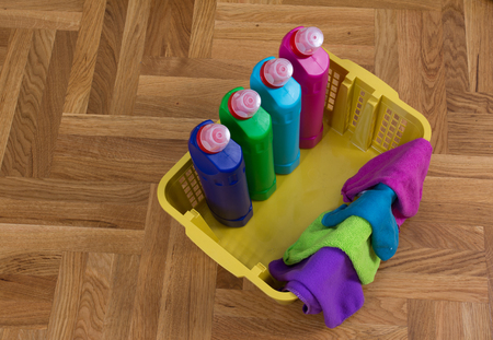 keeping room: Top view of cleaning supplies and cloths in plastic basket on the parquet. House cleaning service concept