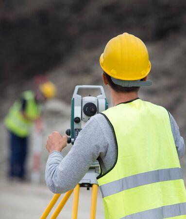 topografo: Ingenieros topógrafos que trabajan con teodolito en el sitio de construcción de carreteras